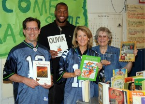 Seattle Seahawks Defensive End Lawrence Jackson surprised Beacon Hill International students with $20,000 worth of new books on Wednesday. L to R: Beacon Hill teacher Andy Pickard, Lawrence Jackson, Librarian Mary Thompson, and Principal Susie Murphy.