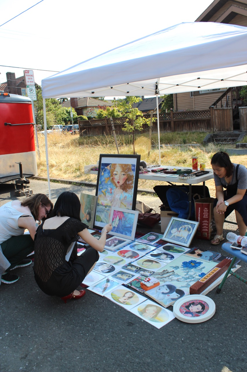 Neighbors checking out the art at a vendor's booth during June's Beacon Art Walkabout. Photo by Wendi Dunlap.